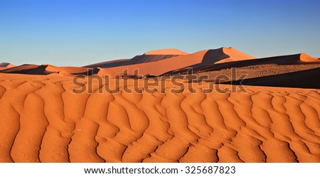 Red sand dunes at sunset casting nice shadows with wind blowing sand at the top in Sossusvlei, Namibia