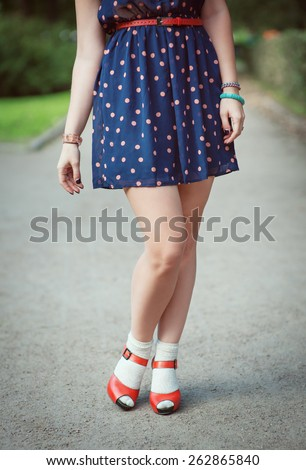 Red sandals with white socks on girl legs in fifties style outdoor - stock photo