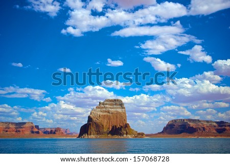 Red sandstone butte emerges from the calm blue water of Lake Powell. - stock photo