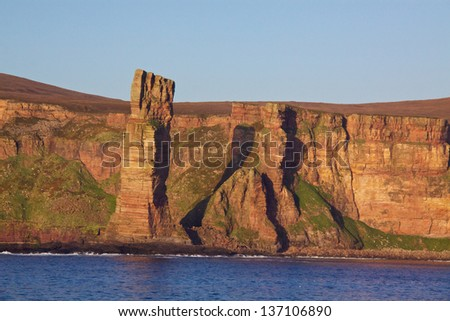 Red sandstone with visible layers on the cliffs of Orkney coast - stock photo
