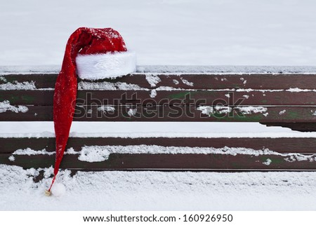 red Santa Claus hat on snow covered bench outdoors - stock photo