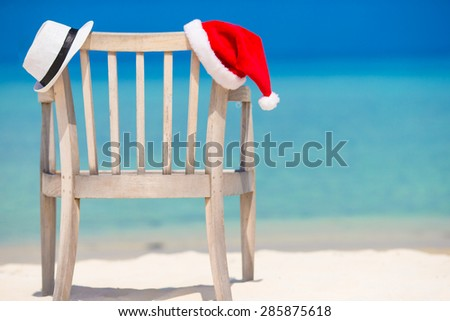 Red santa hat and white straw hat on beach chair at tropical vacation - stock photo