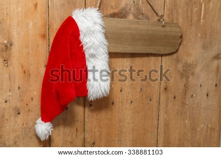 Red Santa hat hanging on a sign on an old front door