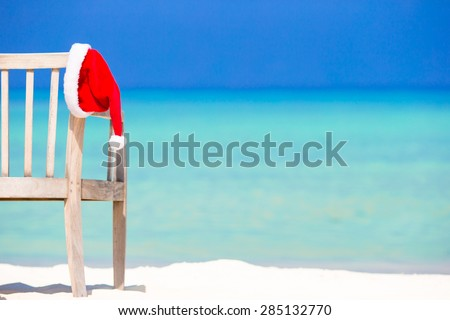 Red santa hat on beach chair at tropical vacation
