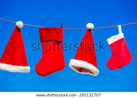 Red Santa hats and Christmas stocking hanging background blue sky