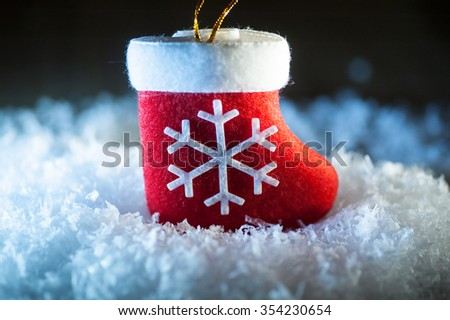 Red Santa's boot with snowflake in snow. - stock photo