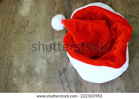 Red Santa's hat on wooden table and copy space
