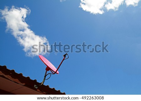 Red satellite dish antenna on the old wood roof on bright blue sky and white cloud.