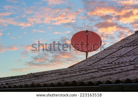Red satellite dish on the rooftop with colorful sky in the background - stock photo