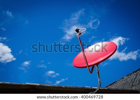 Red Satellite TV Receiver Dish on the Old Tiles Roof - stock photo