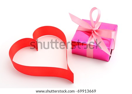 Red satin ribbon heart with pink gift wrapped present on white background