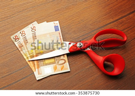 Red scissors cut money on wooden background. Financial concept - stock photo