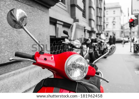 red scooter in the city of Milan with black and white surrounding - stock photo