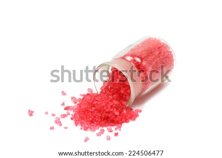 red sea salt in a glass bottle on a white background
