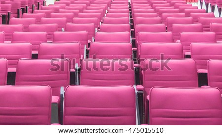 Red seat rows in a bright lecture room.