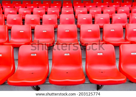 Red seats at the stadium - stock photo