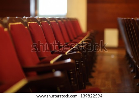 Red seats in an empty theatre in the evening - stock photo