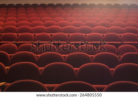Red seats in theater hall with lens flare