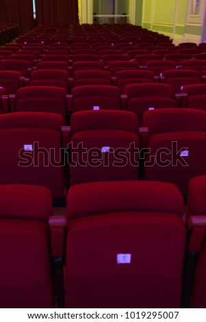 Red seats with numbers in cinema, theater, concert hall. Vertically framed shot