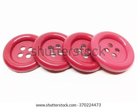 Red sewing buttons on white background.