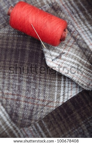 Red sewing spool with needle on a flannel fiber. Close-up photo - stock photo