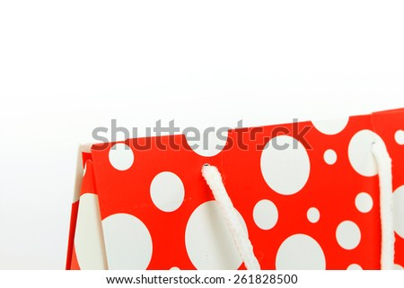Red shopping bag with polka dot design closeup isolated on white - stock photo