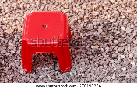 red short stool on stone floor nature background - stock photo