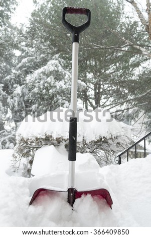 Red shovel close up in the snow on the porch. Deadly blizzard in Washington DC. Virginia  January 23 2016 - stock photo