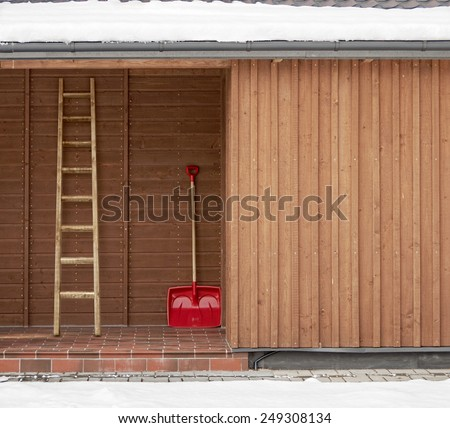 Red shovel wooden ladder near the wooden wall background - stock photo