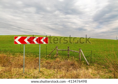 Red sign and wooden fence on the road turn with wonderful green field on the background - stock photo