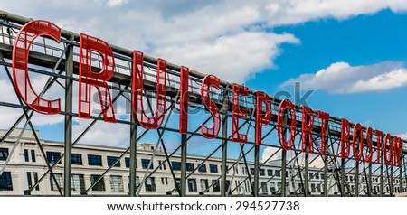 Red sign for the Boston cruise ship port with building and sky in background - stock photo