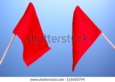 Red signal flags on blue background - stock photo