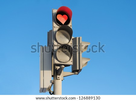 Red signal of a traffic light in the form of heart against the blue sky