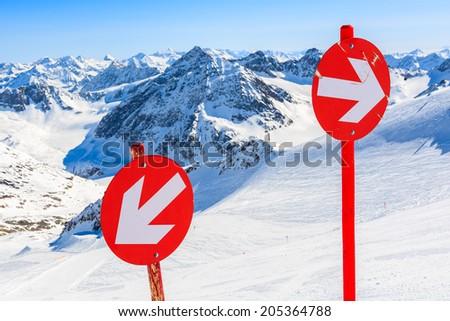 Red signs on ski slope in ski resort of Pitztal, Austrian Alps  - stock photo