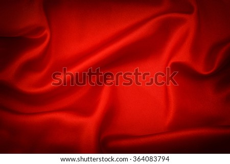 Red silk background. Dark toned with vignette - stock photo