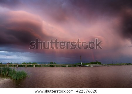 red sky.on the lake. rainbow.  red sunset after the rain. Low key, dark background, spot lighting, and rich Old Masters