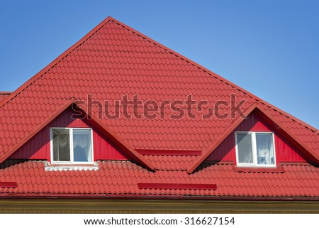 Red slated top of the building with windows - stock photo