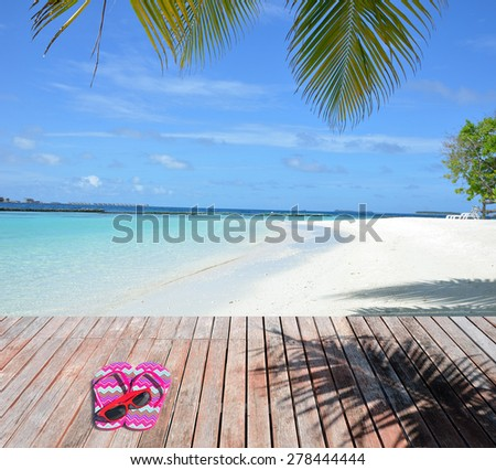 Red slippers and sunglasses on the wooden platform beside tropical beach -- Tropical beach vacation and travel concept   - stock photo
