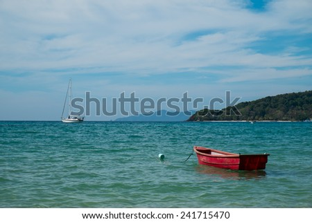 Red small boat on the sea - stock photo