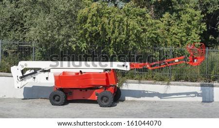 red small mobile cherry picker - stock photo