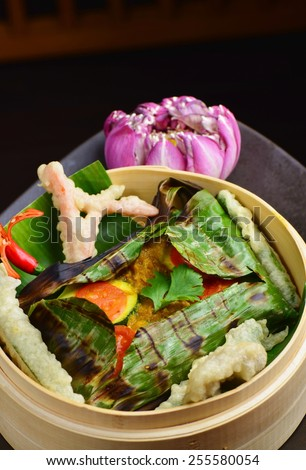 Red snapper fish fillet wraped in banana leaf and vegetable tempura - stock photo