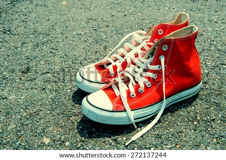 Red sneakers on black background. vintage color