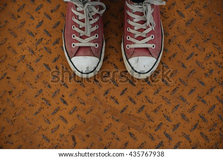 red sneakers on the floor of a shabby iron. background