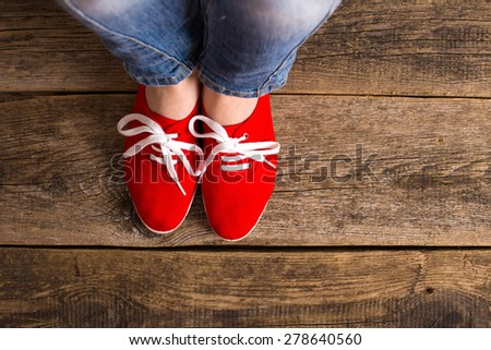 red Sneakers shoes walking on Dirty wooden top view , Canvas shoes walking on wooden - stock photo