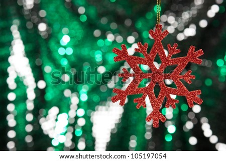 Red snow flake on a green, silver glitter background for Christmas - stock photo