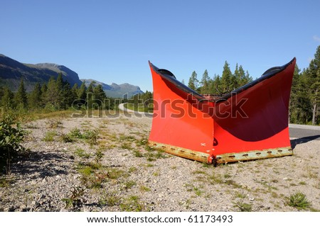 Red snowplow left behind for the next winter. the road leading up to, Ritsem, in northern Sweden. - stock photo