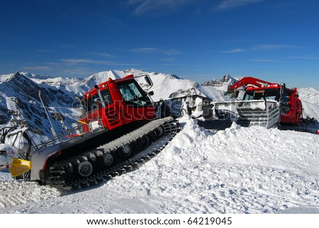 Red snowplows on a slope - stock photo