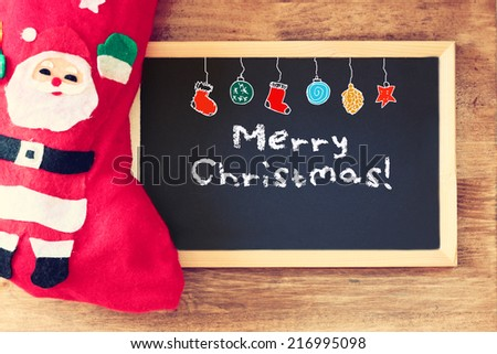 red sock and blackboard with merry christams greeting and colorful icons. christmas card concept - stock photo