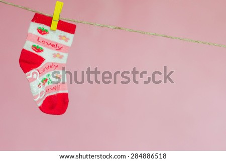Red socks hang on the clothespin pink background - stock photo