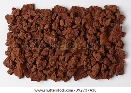 Red Soil isolated on White Background. Pile of Dirt and Stones. Top View of a Heap of Ground. Close Up Macro View with Text or Image Space